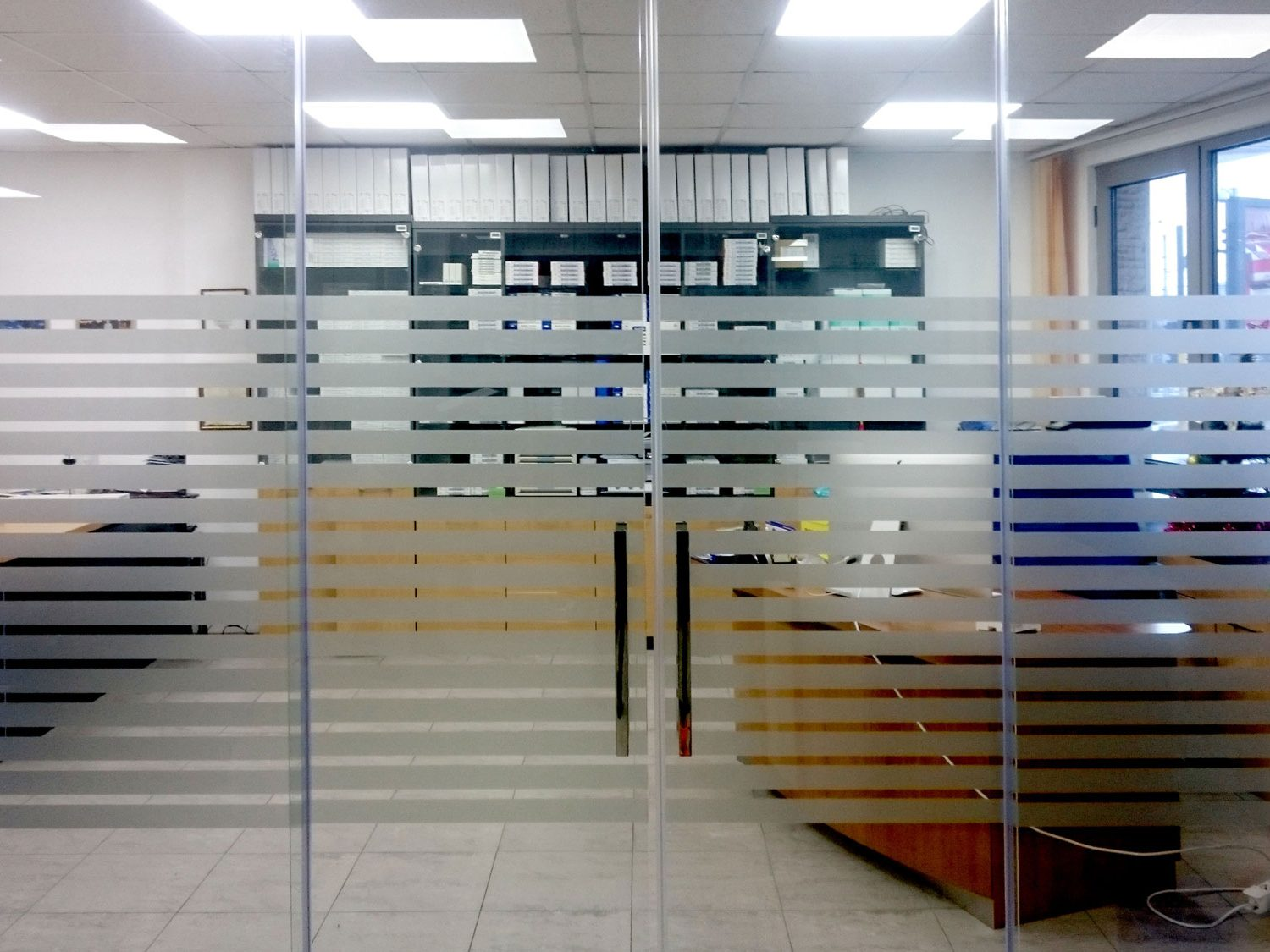 Office glass door decorated with horizontal vinyl lines / фростинг