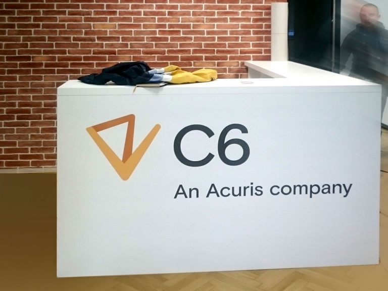 White reception desk branded with large colorful C6 logo