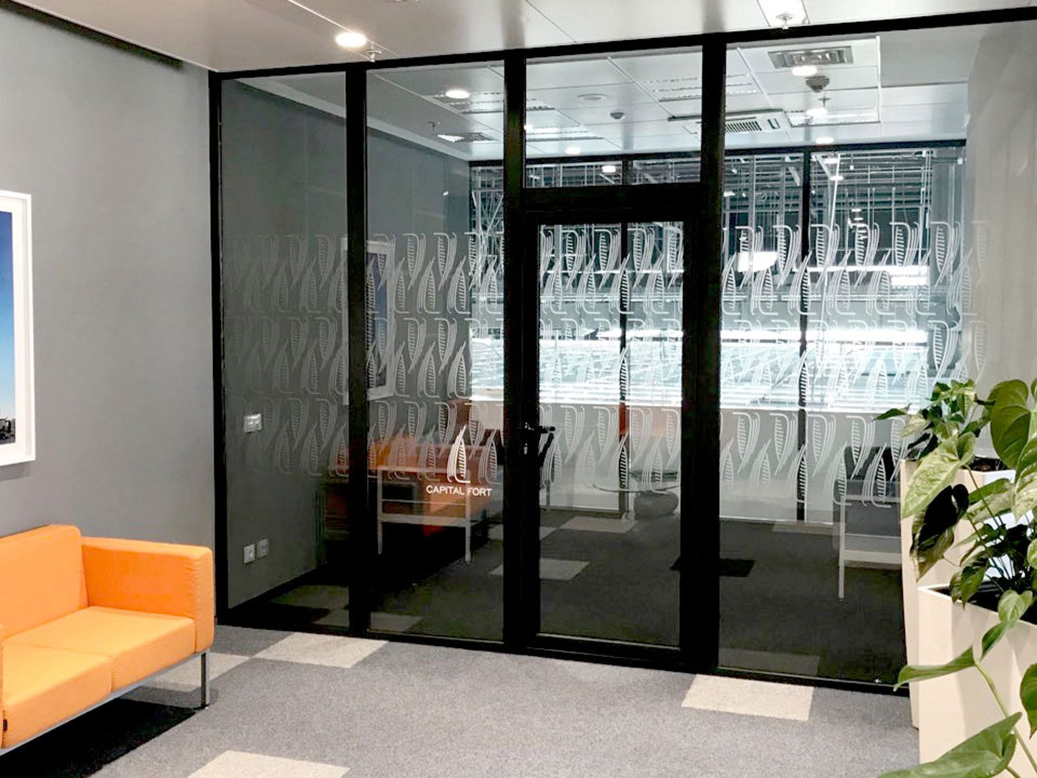 Glass wall decorated with Capital Wall logos