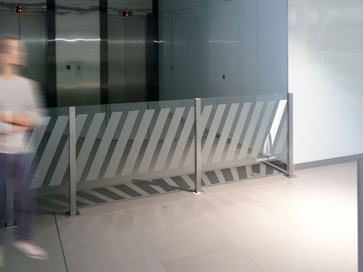 Glass barrier branded with Capital Fort logo and grey diagonal stripes