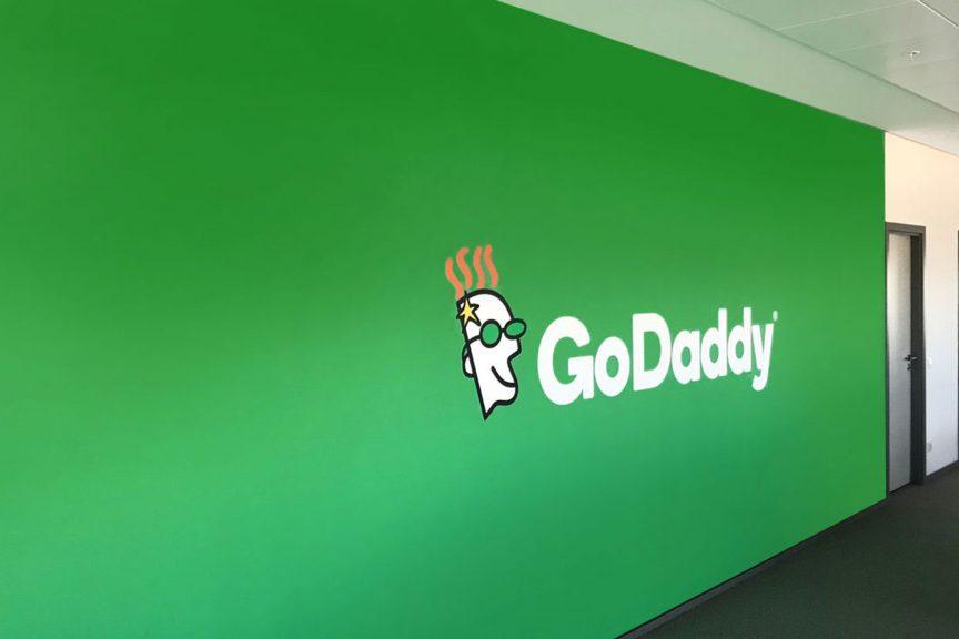 Green wall branded with big GoDaddy logo