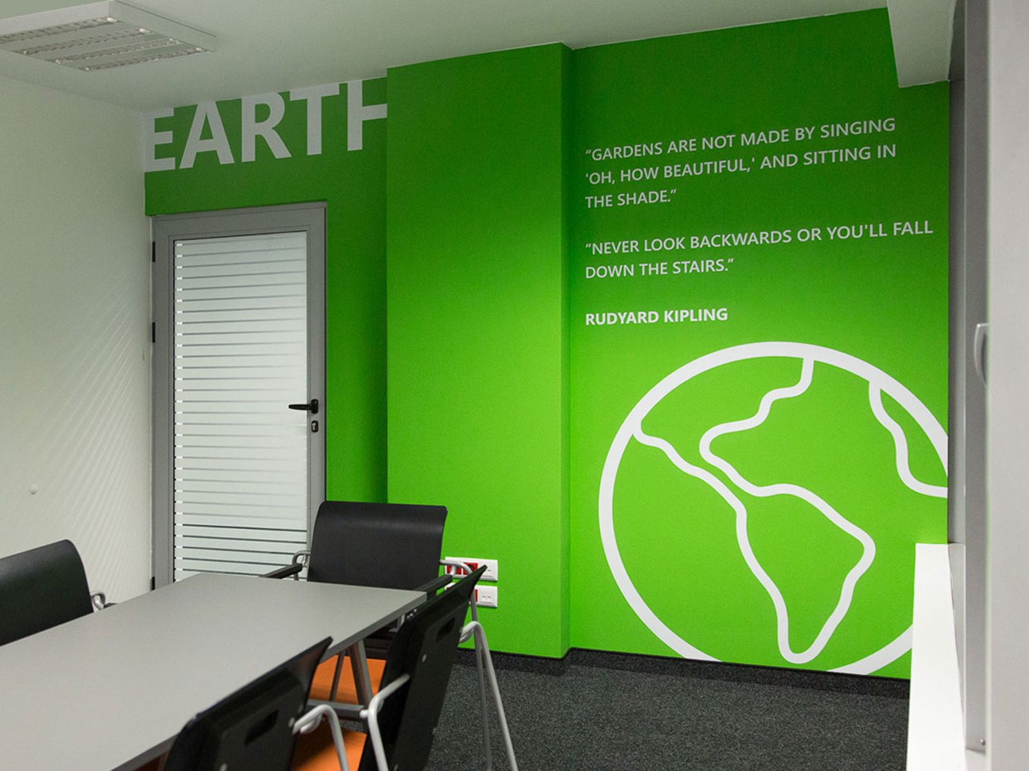 Meeting room with green wall dedicated to earth with Rudyard Kipling quote