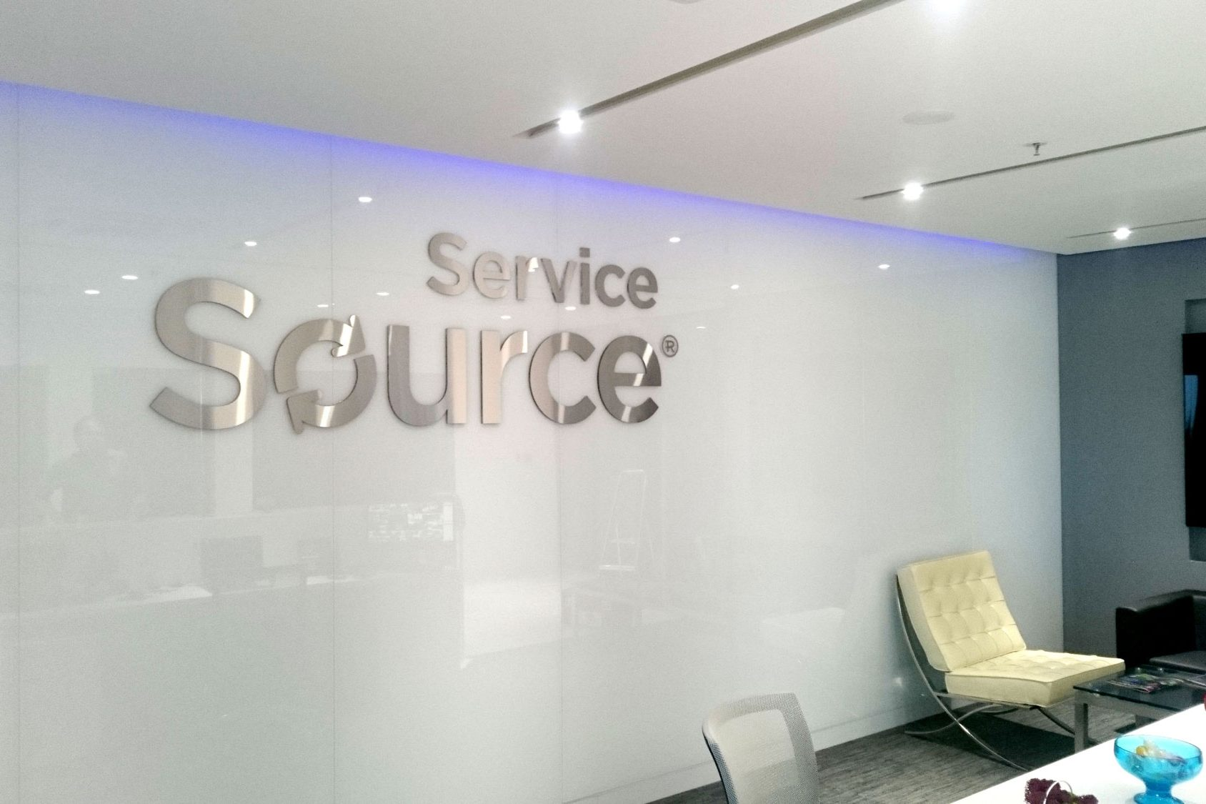 Large metal logo of Service Source on white wall