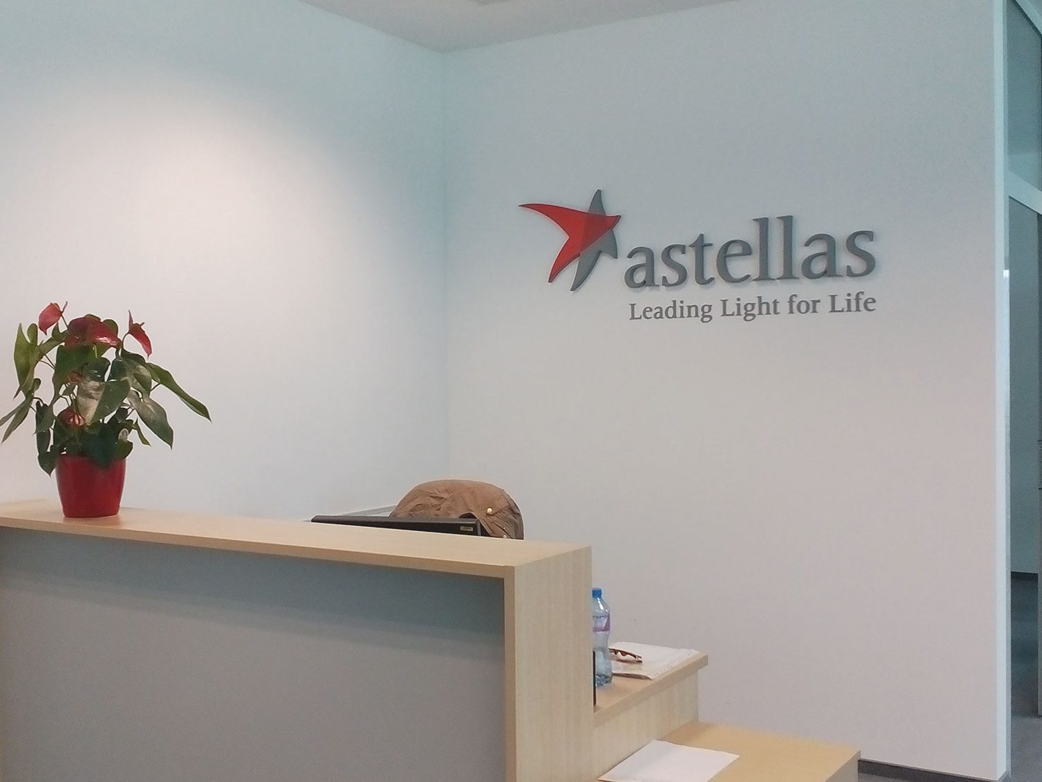 Astellas logo on the wall behind the reception desk